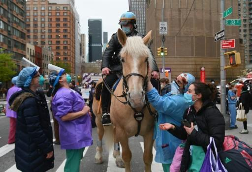 Healthcare workers pet a NYPD horse as people cheer and applaud to show their gratitude to essential workers outside NYU Langone Health hospital in New York City