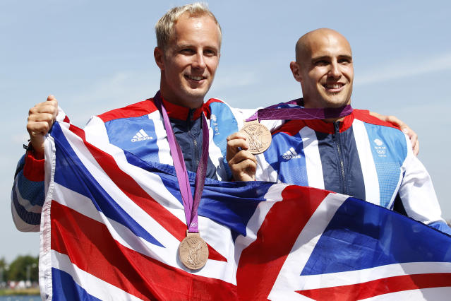 Bronze medallists Britain's Liam Heath (R) and Jon Schofield stand on the podium during the victory ceremony for the men's kayak double (K2) 200m final at the Eton Dorney during the London 2012 Olympic Games August 11, 2012. REUTERS/Jim Young (BRITAIN - Tags: OLYMPICS SPORT CANOEING)
