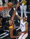 Los Angeles Clippers guard Terance Mann (14) dunks on Utah Jazz center Rudy Gobert, left, during the second half of Game 5 of a second-round NBA basketball playoff series Wednesday, June 16, 2021, in Salt Lake City. (AP Photo/Rick Bowmer)