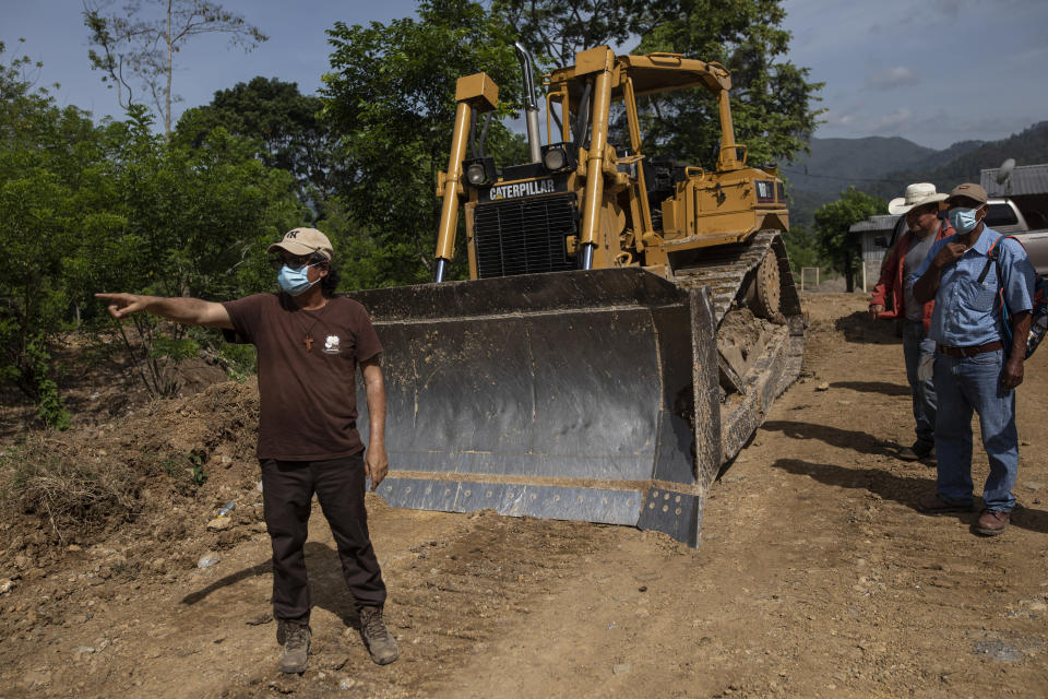 Friar Leopoldo Serrano shows bulldozer operators which direction he would like them to pave a road for a new community being constructed for the residents of La Reina, whose homes were devastated by a mudslide triggered by Hurricanes Eta and Iota, in Mission San Francisco de Asis, Honduras, Tuesday, June 22, 2021. Twenty-five years ago, the powerful local cartel run by Arnulfo Valle bought the 70 acres adjacent to the mission where Father Serrano hopes to put those displaced from La Reina. (AP Photo/Rodrigo Abd)