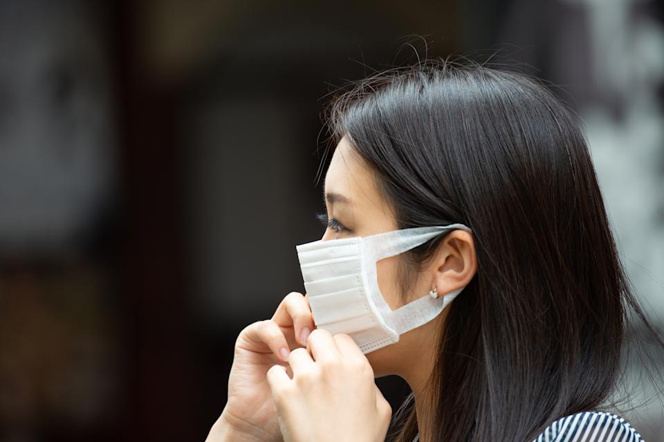 Asian woman putting on face mask