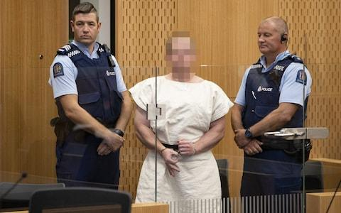 <span>Brenton Tarrant, gestures as he is lead into the dock for his appearance for murder in the Christchurch District Court on March 16, 2019</span> <span>Credit: Getty </span>