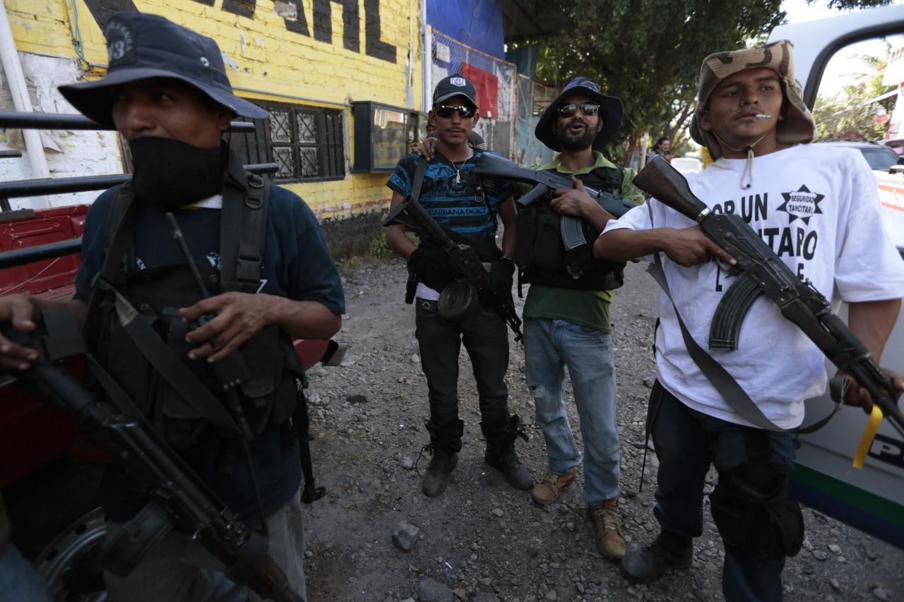 Members of the community police, acting in this case as vigilantes, stand together after breaking into the village of Paracuaro, and taking over, in Michoacan state, January 4, 2014. Some 100 gunmen of the community police from different towns, riding in a convoy of trucks entered Paracuaro and disarmed the police to gain control over the town in an effort to rid the area of the Knights Templar cartel (Caballeros Templarios), according to local media. Michoacan has been rocked by repeated explosions of civil unrest in 2013 and vigilante groups have sprung up in the region which complain that state and federal police are not protecting them from the gangs. 