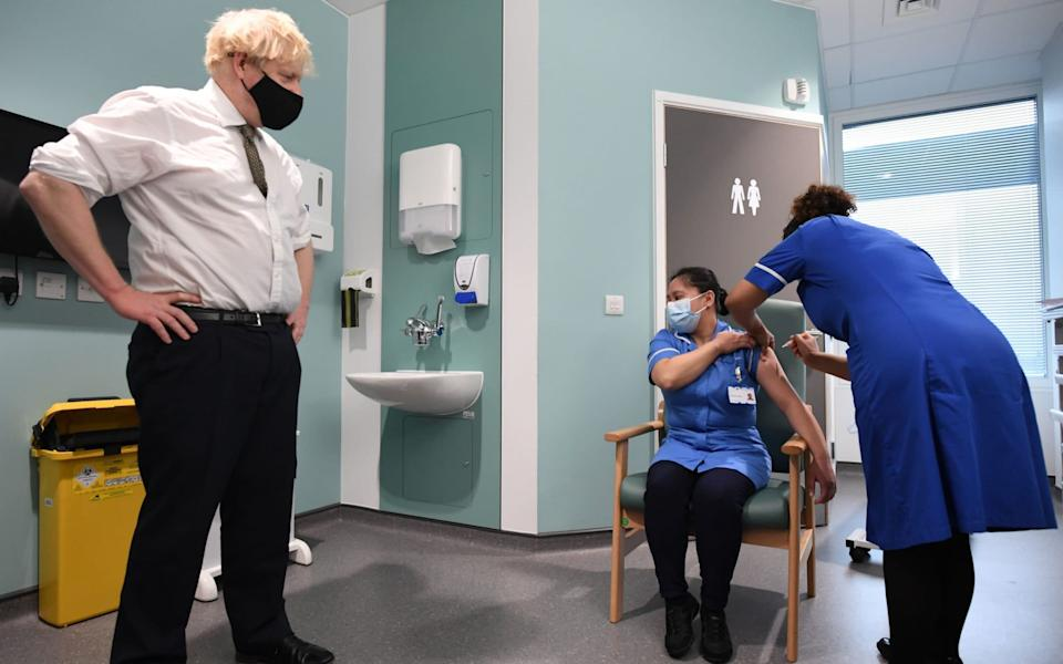Boris Johnson watches as Jennifer Dumasi is injected with the Oxford/AstraZeneca Covid-19 vaccine during a visit to Chase Farm Hospital in north London - Stefan Rousseau/PA Wire