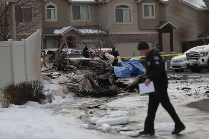 An investigator walks near the debris from a small private plane that crashed in a residential area Wednesday, Jan. 15, 2020, in Roy, Utah. The small plane crashed Wednesday, killing the pilot as the aircraft narrowly avoided hitting any townhomes, authorities said. (Ben Dorger/Standard-Examiner via AP)