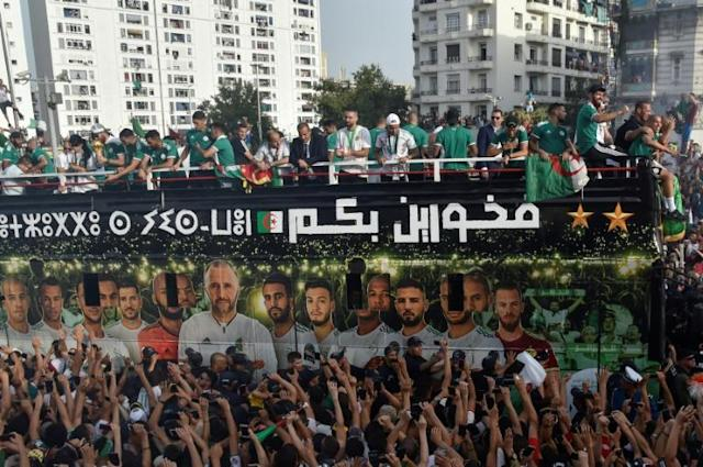 Algeria's national team players greet fans lining the streets during an open-top bus parade in the capital Algiers following their Africa Cup triumph (AFP Photo/RYAD KRAMDI )