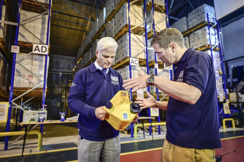 International Development Minister Desmond Swayne (left) is shown a Lifesaver Cube by Head of Humanitarian Response DFID Dylan Winder (right) during a visit to DFID's UK Disaster Response Operations Centre at Cotswold Airport, Kemble.