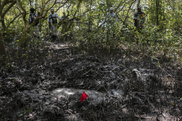Soldiers of the Mexican Army and members of the National Guard stand next to a clandestine grave site in Puquita, a tropical mangrove island near Alvarado in the Gulf coast state of Veracruz, Mexico, Thursday, Feb. 18, 2021. Investigators from the National Search Commission found three pits with human remains and plastic bags inside. The number of bodies there has not yet been determined. (AP Photo/Felix Marquez)