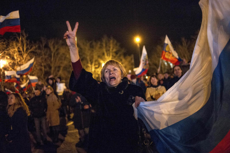 Pro-Russian people celebrate in the central square in Sevastopol, Ukraine, late Sunday, March 16, 2014. Russian flags fluttered above jubilant crowds Sunday after residents in Crimea voted overwhelmingly to secede from Ukraine and join Russia. The United States and Europe condemned the ballot as illegal and destabilizing and were expected to slap sanctions against Russia for it.(AP Photo/Andrew Lubimov)