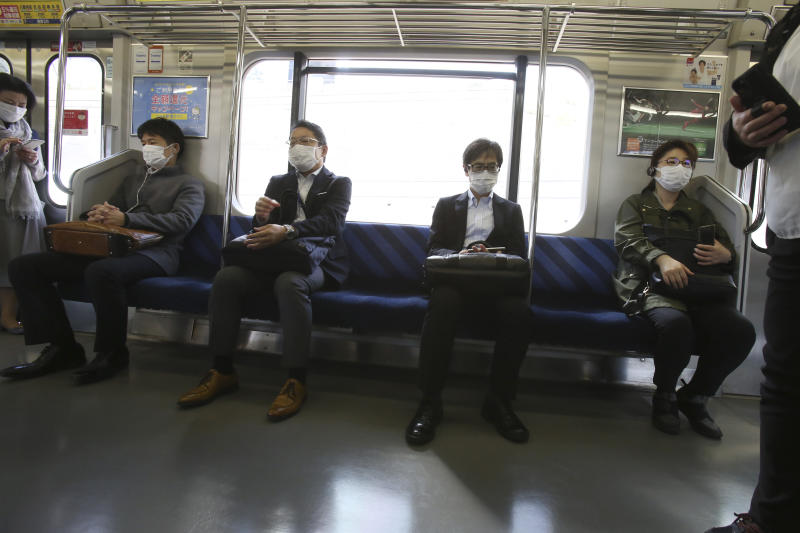 Passengers wearing face masks to protect against the spread of the new coronavirus ride on a train in Yokohama near Tokyo, Wednesday, April 8, 2020. The new coronavirus causes mild or moderate symptoms for most people, but for some, especially older adults and people with existing health problems, it can cause more severe illness or death. (AP Photo/Koji Sasahara)