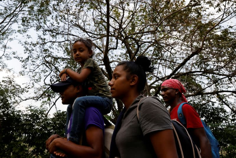 FILE PHOTO: Arony Maude from Honduras is carried by her uncle along a motorway in El Ceibo while making their way to the U.S.