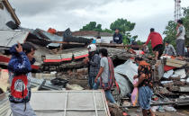 Residents inspect the ruin of a building damaged by an earthquake in Mamuju, West Sulawesi, Indonesia, Saturday, Jan. 16, 2021. Damaged roads and bridges, power blackouts and lack of heavy equipment on Saturday hampered Indonesia's rescuers after a strong and shallow earthquake left a number of people dead and injured on Sulawesi island. (AP Photo/Yusuf Wahil)