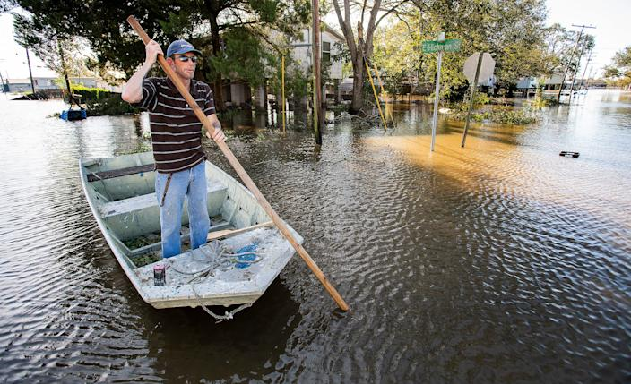 Len Moneaux poles his boat along a flooded street as he checks on neighbors in Delcambre, Louisiana, on Saturday morning Oct. 10, 2020, after Hurricane Delta hit the Louisiana Coast overnight.