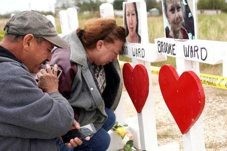 Lorenzo Flores and Terrie Smith react at a line of crosses in remembrance of those killed in the shooting at the First Baptist Church of Sutherland Springs