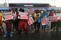 Demonstrators carry banners and shout slogans during a protest over alleged police brutality, in Lagos