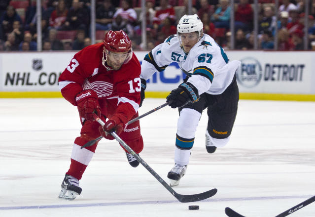 Detroit Red Wings forward Pavel Datsyuk (13), of Russia, reaches for the puck, defended by San Jose Sharks forward Tommy Wingels (57), during the first period of an NHL hockey game in Detroit, Mich., Monday, Oct. 21, 2013. (AP Photo/Tony Ding)