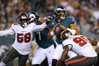 Philadelphia Eagles quarterback Jalen Hurts (1) looks to pass under pressure from Tampa Bay Buccaneers outside linebacker Shaquil Barrett (58) during the first half of an NFL football game Thursday, Oct. 14, 2021, in Philadelphia. (AP Photo/Matt Rourke)