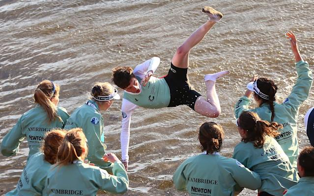 <span>Cambridge women throw cox Matthew Holland into the Thames</span> <span>Credit: GETTY IMAGES </span>