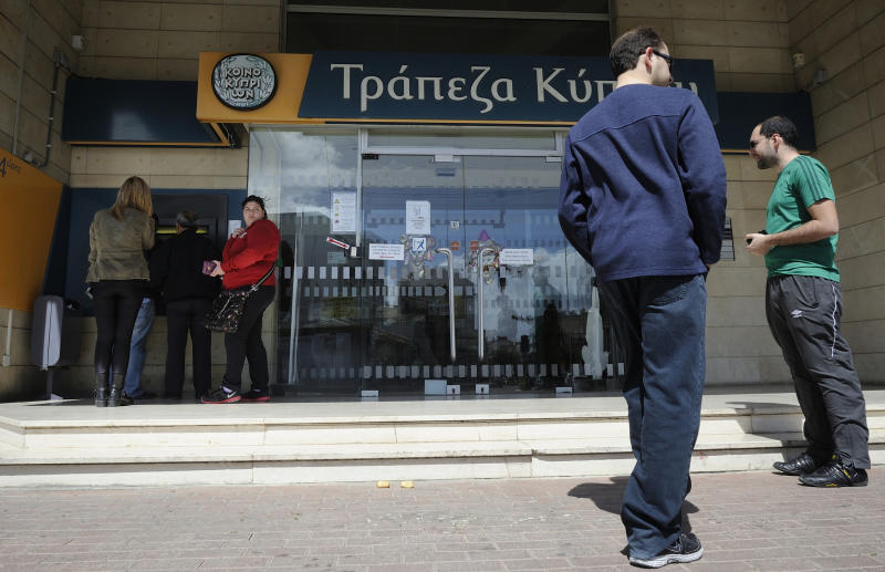 In this image taken Saturday, March 16, 2013,  people queue to use an ATM machine outside of Bank of Cyprus branch in southern port city of Limassol, Saturday, March 16, 2013. Many rushed to cooperative banks which are open Saturdays in Cyprus after learning that the terms of a bailout deal that the cash-strapped country hammered out with international lenders includes a one-time levy on bank deposits. The move, decided in an extraordinary meeting of the finance ministers of the 17-nation eurozone in the early hours Saturday, is a major departure from established policies. Analysts have warned that making depositors take a hit threatens to undermine investors' confidence in other weaker eurozone economies and might possibly lead to bank runs. (AP Photo/Pavlos Vrionides)