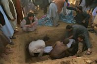 Relatives lower a body into a grave in Kunduz (AFP/Hoshang Hashimi)
