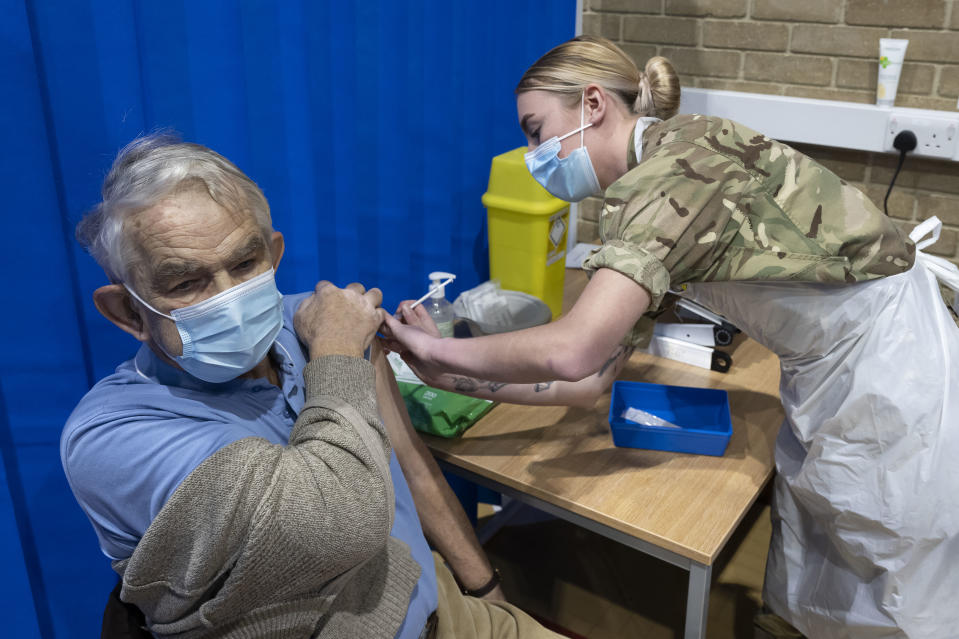 CARDIFF, WALES - FEBRUARY 03: A member of the military vaccinates a man at the COVID-19 mass vaccination centre at Pentwyn Leisure Centre on February 3, 2021 in Cardiff, Wales. Nearly 440,000 people in the top priority groups have been given their first doses of Covid-19 vaccines in Wales so far. The aim is to have just under 750,000 people, including health workers and people aged over 70, given a first dose by mid-February. (Photo by Matthew Horwood/Getty Images)