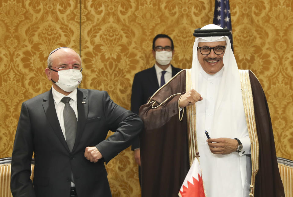Israel's national security adviser, Meir Ben-Shabbat, left, bumps elbows with Bahrain's Foreign Minister Abdullatif al-Zayani after signing an agreement in Manama, Bahrain, Sunday, Oct. 18, 2020. Israel and Bahrain signed an agreement establishing formal diplomatic relations, making the Gulf country the fourth Arab state to normalize ties with Israel. (Ronen Zvulun/Pool Photo via AP)