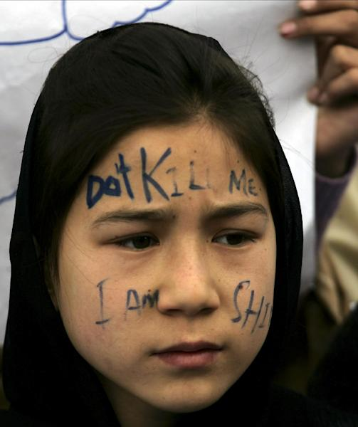 """A Pakistani Shiite girl takes part in a sit-in protest with others to condemn the Saturday bombing which killed scores of people, in Quetta, Pakistan on Monday, Feb. 18, 2013. The families of the bombing victims have refused to bury their loved ones until authorities take action against the militants who were responsible. Mispelled and partially shown writing reads, """"don't kill me. I am Shia."""" (AP Photo/Arshad Butt)"""