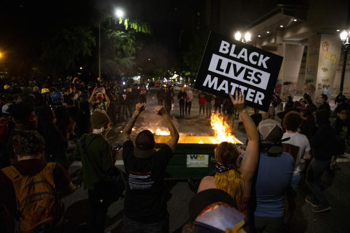 A waste receptacle's contents are in flames as protesters gather in downtown Portland, Ore. on July 10, 2020. (Dave Killen/The Oregonian via AP)