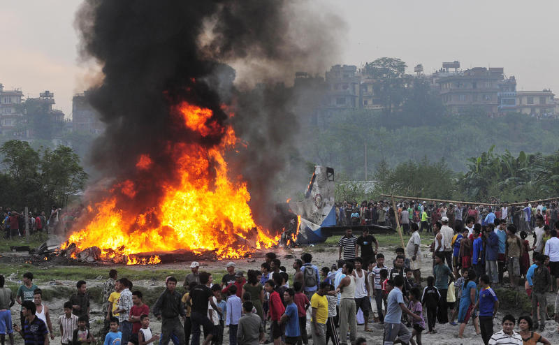 Nepalese gather around the burning wreckage at the crash site of a Sita Air airplane near Katmandu, Nepal, early Friday, Sept. 28, 2012. The plane carrying trekkers to the Everest region crashed and burned just after takeoff Friday morning in Nepal's capital, killing the 19 Nepali, British and Chinese people on board, authorities said. (AP Photo)