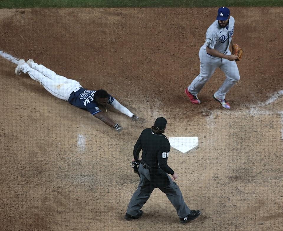 Randy Arozarena slides into home to score the winning run of an 8-7 victory over the Dodgers.