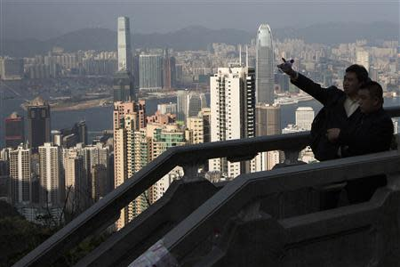 A mainland Chinese businessman points at a building from the Peak, a popular sightseeing spot for tourists, in Hong Kong