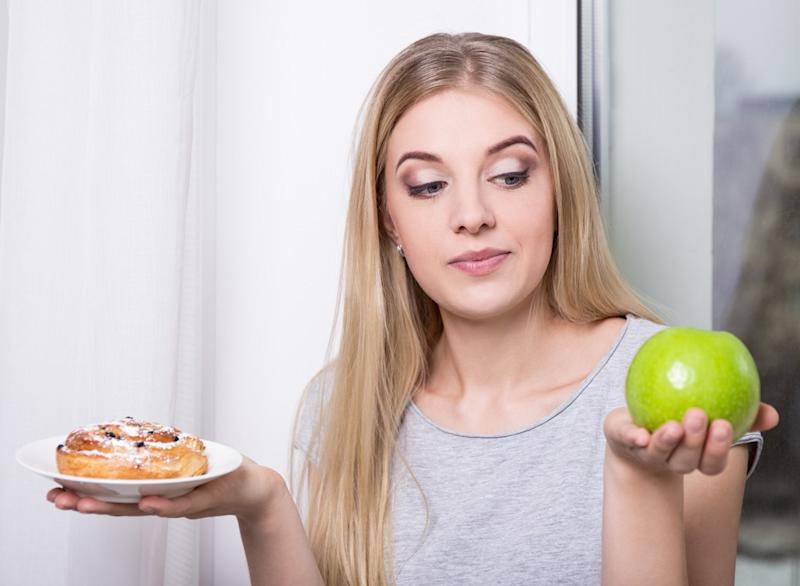 woman choosing apple over a sweet pastry
