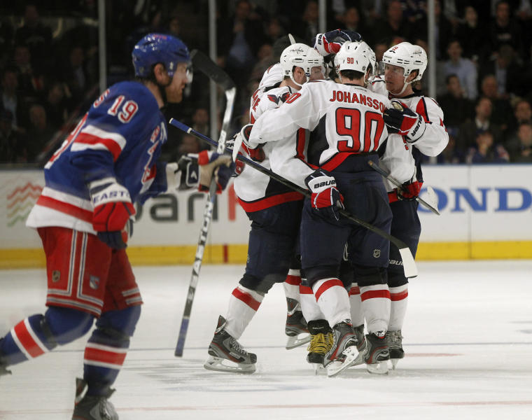 New York Rangers center Brad Richards (19) skates away as Washington Capitals celebrate around teammate Alex Ovechkin, after Ovechkin scored the winning goal in the third period of Game 2 of the NHL Eastern Conference semifinals at Madison Square Garden in New York, Monday, April 30, 2012. The Capitals defeated the Rangers 3-2. (AP Photo/Kathy Willens)