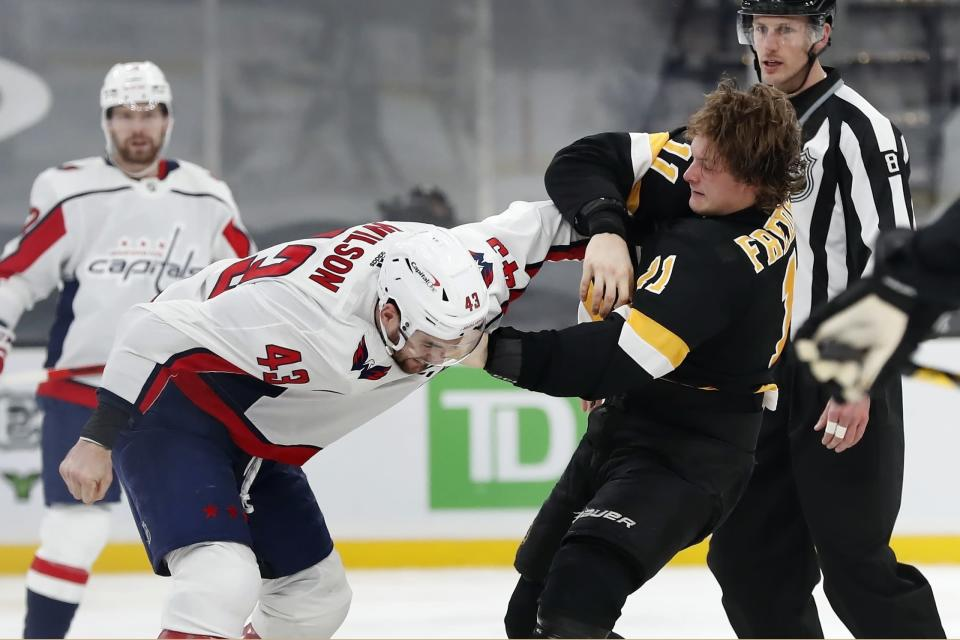 FILE - Boston Bruins' Trent Frederic (11) and Washington Capitals' Tom Wilson (43) fight during the third period of an NHL hockey game in Boston, in this Friday, March 5, 2021, file photo. The Boston Bruins and Washington Capitals already have bad blood built up going into their first-round playoff series that starts Saturday night. Game 1 will be Boston defenseman Brandon Carlo's first time on the ice against Tom Wilson since the Washington forward concussed him with a hit in March that drew a seven-game suspension. (AP Photo/Michael Dwyer, File)