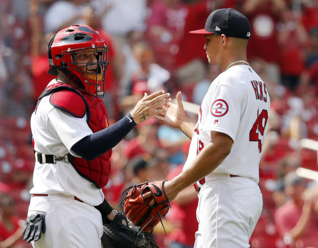 St. Louis Cardinals catcher Yadier Molina, left, and relief pitcher Jordan Hicks celebrate following a baseball game against the Cincinnati Reds, Sunday, July 15, 2018, in St. Louis. (AP Photo/Jeff Roberson)
