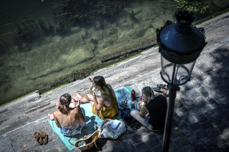 Europeans have thronged parks and rivers, as here on the banks of the River Seine in Paris, as the rising mercury announces the start of summer