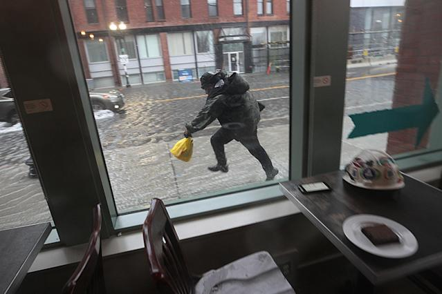 <p>A man dashes through rising waters on a flooded Causeway Street in Boston, as seen through a coffee shop window, during a nor'easter storm on March 2, 2018. (Photo: Suzanne Kreiter/The Boston Globe via Getty Images) </p>