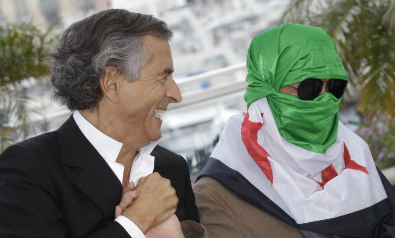 Director Bernard-Henry Levy, left, and an unidentified person wearing a Syrian flag pose during a photo call for The Oath of Tobruk at the 65th international film festival, in Cannes, southern France, Friday, May 25, 2012. (AP Photo/Lionel Cironneau)