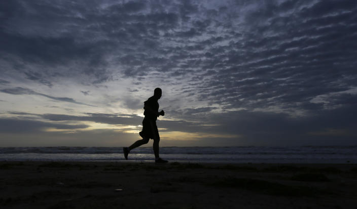 A man runs along the beach at sunrise, Monday, July 27, 2020, in South Padre Island, Texas. Hurricane Hanna passed through the area leaving heavy rains but has been downgraded to a tropical storm as it moves into Mexico. (AP Photo/Eric Gay)