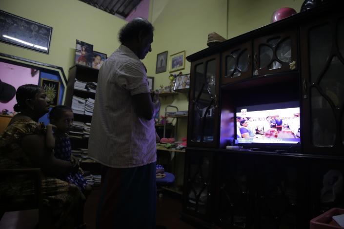 Sri Lankan family follow breaking news in television in Colombo, Sri Lanka, Friday, Oct. 26, 2018. Sri Lankan President Maithripala Sirisena has sacked the country's prime minister and replaced him with a former strongman, state television said Friday. (AP Photo/Eranga Jayawardena)