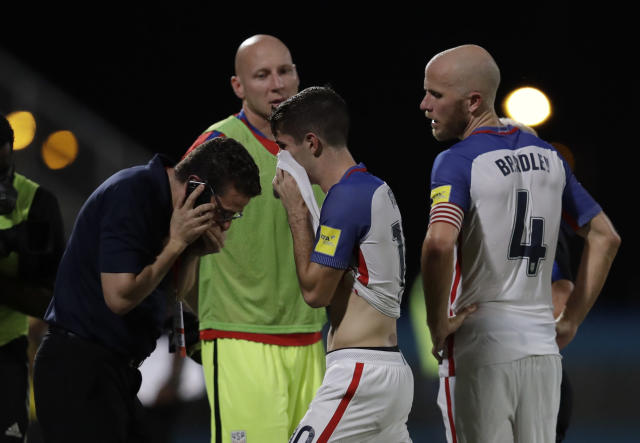 "United States' <a class=""link rapid-noclick-resp"" href=""/soccer/players/christian-pulisic/"" data-ylk=""slk:Christian Pulisic"">Christian Pulisic</a>, center, and his teammate United States' <a class=""link rapid-noclick-resp"" href=""/soccer/players/michael-bradley"" data-ylk=""slk:Michael Bradley"">Michael Bradley</a>, right, walk on the pitch after losing 2-1 against Trinidad and Tobago during a 2018 World Cup qualifying soccer match  in Couva, Trinidad, Tuesday, Oct. 10, 2017. (AP Photo/Rebecca Blackwell)"