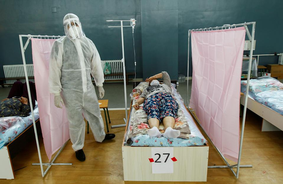 A medical specialist wearing personal protective equipment (PPE) treats patients at a day hospital, which is located in a school gym and provides services free of charge, in Bishkek, Kyrgyzstan July 16, 2020. The opening of the medical facility amid the coronavirus disease (COVID-19) outbreak was initiated by local businessmen, who currently provide its funding, which includes the purchase of pharmaceuticals, equipment and salaries payment. REUTERS/Vladimir Pirogov     TPX IMAGES OF THE DAY