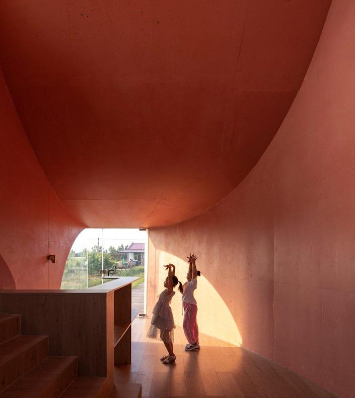 Two young girls rehearse their dance moves inside the contemporary Peach Hut pavilion.
