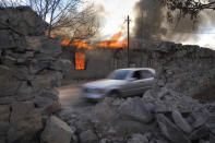 Smoke and flame rises from a burning house in an area once occupied by Armenian forces but soon to be turned over to Azerbaijan, in Karvachar, the separatist region of Nagorno-Karabakh, on Friday, Nov. 13, 2020. Under an agreement ending weeks of intense fighting over the Nagorno-Karabakh region, some Armenian-held territories adjacent to the region are passing to Azerbaijan. (AP Photo/Dmitry Lovetsky)