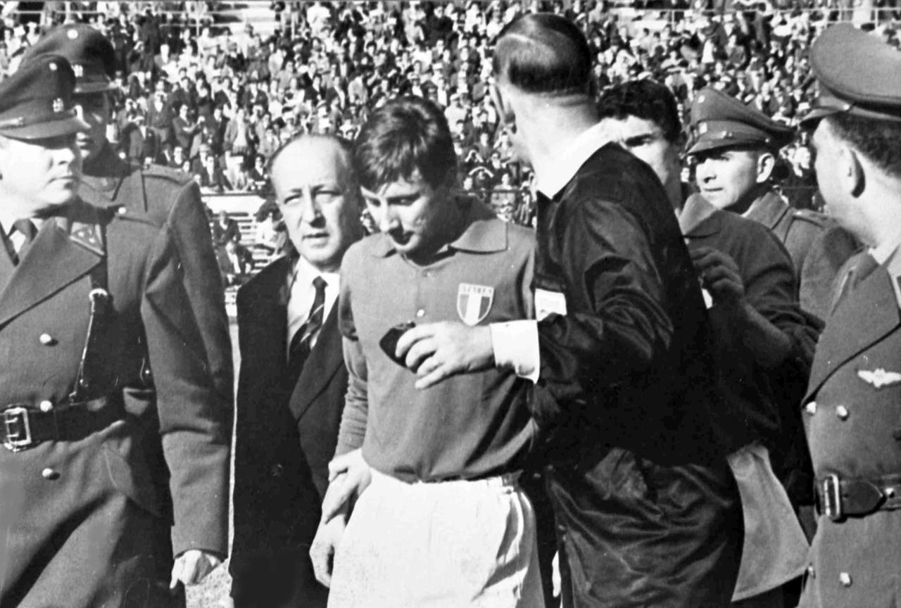 FILE - In this file photo from June 2, 1962, Italian forward Giorgio Ferrini, center, is sent off by British referee Ken Aston, back to camera, after an incident during the first half of the World Cup match between Italy and Chile in Santiago, Chile. Ferrini refused to leave the field after being ordered off by the referee and was removed by police officers. (AP Photo, File)