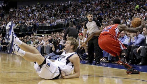 Dallas Mavericks' Dirk Nowitzki, of Germany, falls to the court after being stripped of the ball by Los Angeles Clippers' Eric Bledsoe, right, in the first half of an NBA basketball game Monday, April 2, 2012, in Dallas. (AP Photo/Tony Gutierrez)