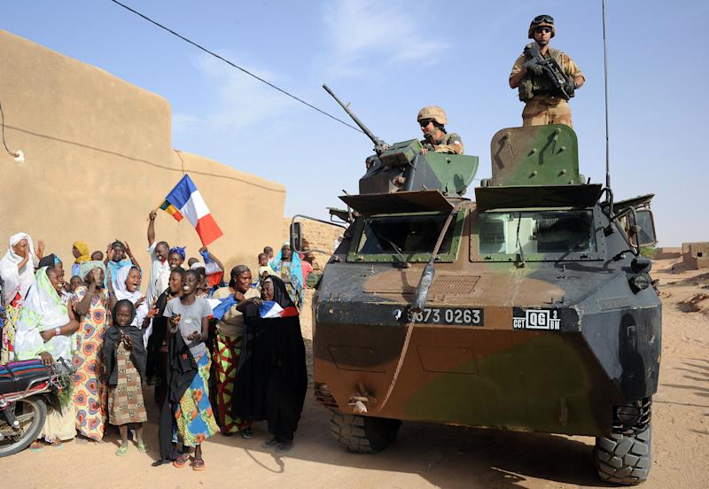 Locals welcome with French flags, French soldiers on top of a armored vehicle in Diabaly, northern Mali, Sunday, Feb. 17, 2013. Mali's military detained eight Arab men last week in Timbuktu, raising fears of further reprisals against the region's Arab minority whose members are accused of having supported the al-Qaida-linked groups which overran northern Mali last year. (AP Photo /Pascal Guyot, Pool)