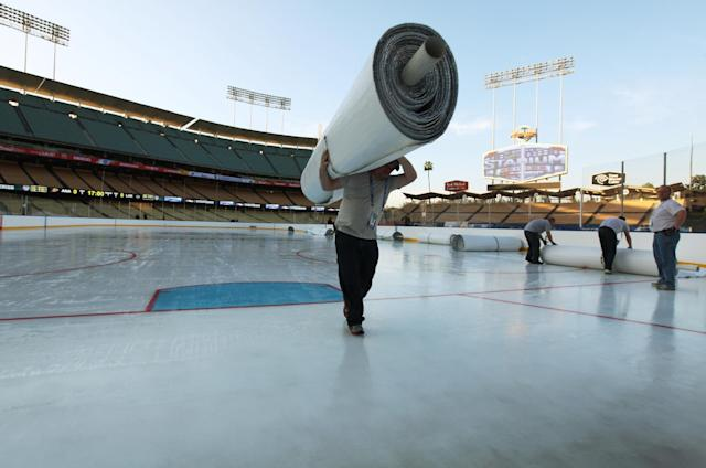 A worker carries a roll of mylar that protected a hockey rink at Dodger Stadium from daytime temperatures in the high 70s Fahrenheit, as preparations continue for the upcoming 2014 NHL Stadium Series hockey game in Los Angeles Wednesday, Jan. 22, 2014. The Los Angeles Kings and Anaheim Ducks will play outdoors at Dodger Stadium next Saturday, Jan. 25th. (AP Photo/Nick Ut)