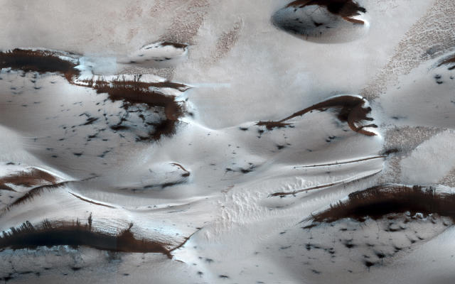 <p>Mars' northern-most sand dunes are seen as they begin to emerge from their winter cover of seasonal carbon dioxide (dry) ice in this image acquired by the HiRISE camera aboard NASA's Mars Reconnaissance Orbiter January 16, 2014. The steep lee sides of the dunes are also ice-free along the crest, allowing sand to slide down the dune. Dark splotches are places where ice cracked earlier in spring, releasing sand, according to a NASA news release. (Photo: NASA/JPL-Caltech/Univ. of Arizona/Reuters) </p>
