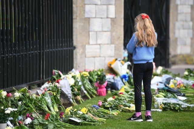 A young girl looks at flowers at Cambridge Gate at Windsor Castle